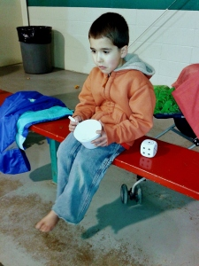 This is Elias at a Saturday morning hockey game (that his daddy, grandpa, auntie and uncle were playing in), eating a bowl of oatmeal in his bare feet. He's way too cute.